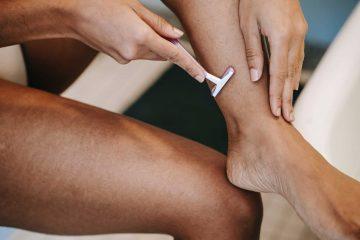 Een transvrouw die haar benen scheert
